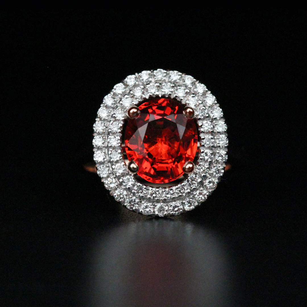 Bague en or rose 18K sertie d'un saphir orange taille ovale de 2,73Ct et d'un double entourage de diamants